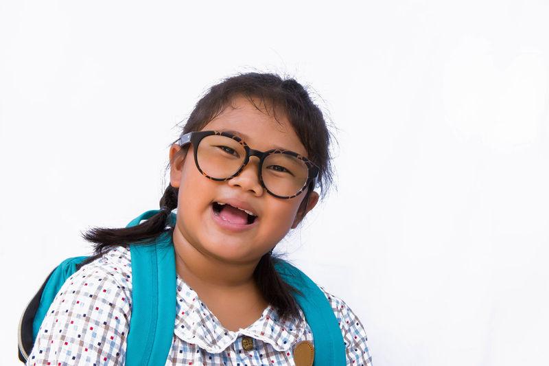 Portrait Of Happy Girl Wearing Eyeglasses Against White Background