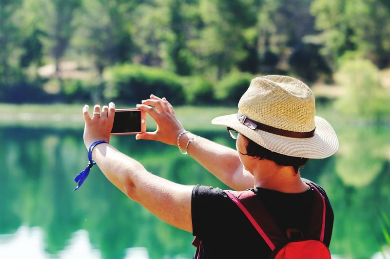 Rear view of woman photographing lake