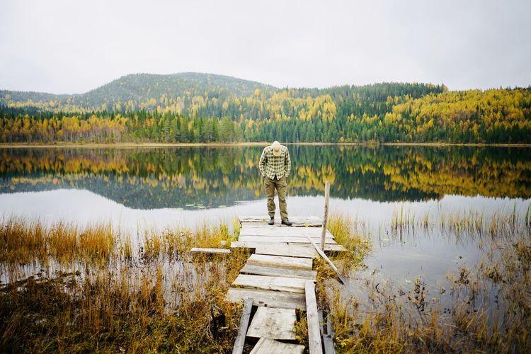 Full length of man standing on pier by lake against sky