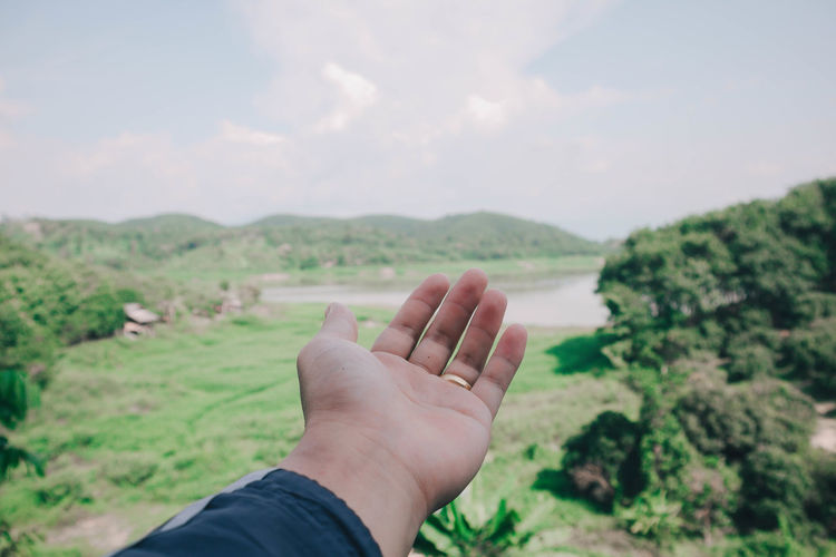 Close-up of person gesturing over land against sky