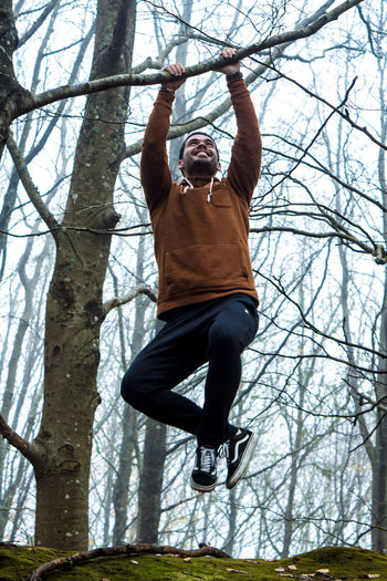 Low angle view of man jumping on bare tree