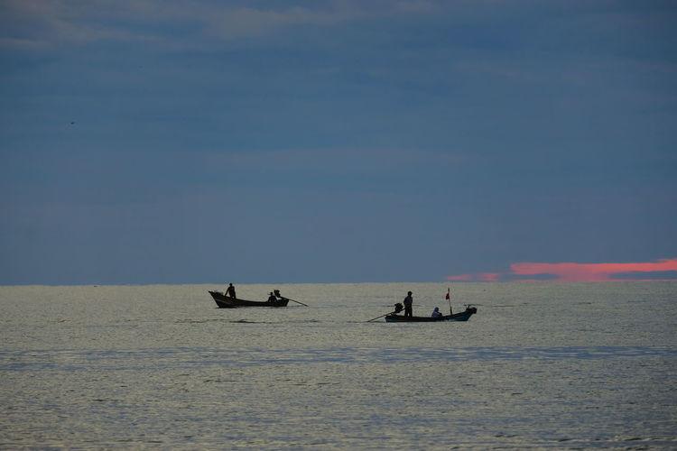 People sailing in sea against sky