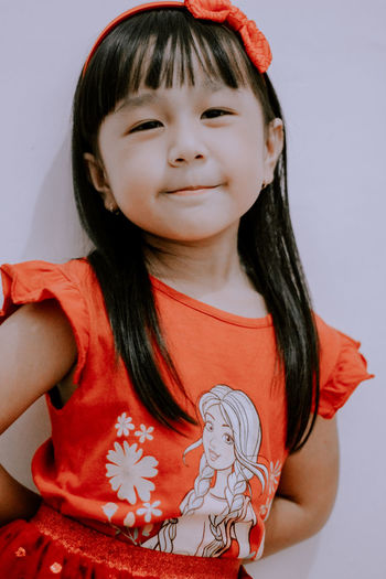 Portrait of cute girl against red wall