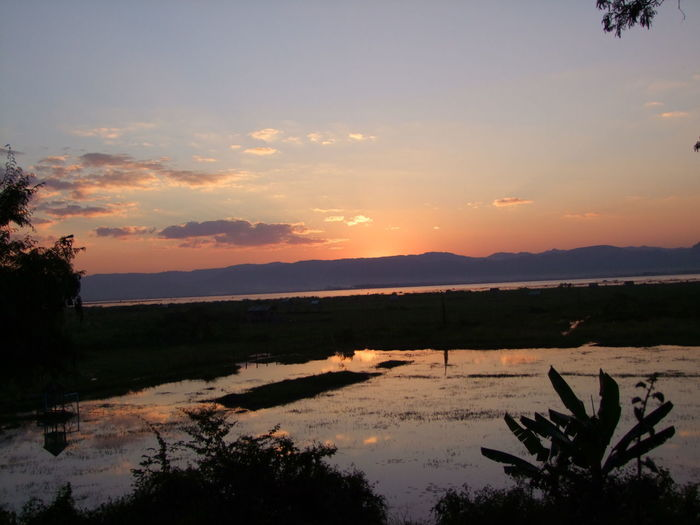 Sunset over Inle Lake Beauty In Nature Blue And Orange Sky Disappearing Sun Evening Light Inle Lake Lake Mountain Range Myanmar Orange Reflection In The Water Peaceful Evening Peaceful Place Peaceful View Shrine Silhouettes Sunset Landscape Sunset Light Tourism Tourist Attraction  Tourist Destination Tranquil Tranquil Scene Tranquility Travel Destination Tree Water