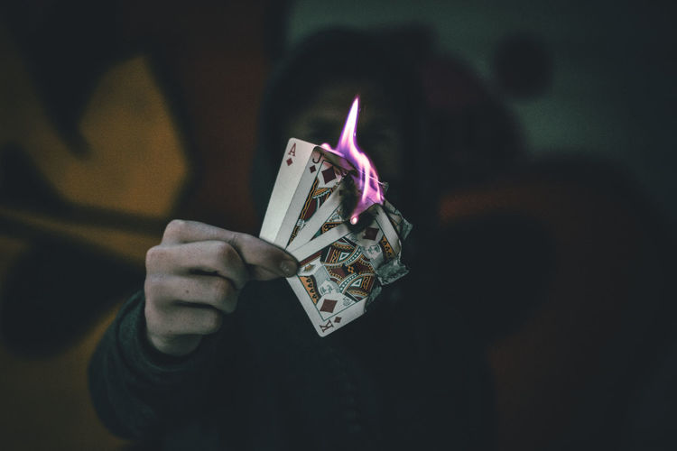 Close-up of person holding burning cards