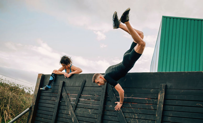 Two participants in an obstacle course climbing a wall Obstacle Race Obstacle Course Ocr Collaboration Cooperation Runner Sport Horizontal Extreme Sports Outdoors Competition Athletic Training Workout Strong Boot Camp Effort Power Determination Climbing Wall Two People Jumping Flying Woman Man