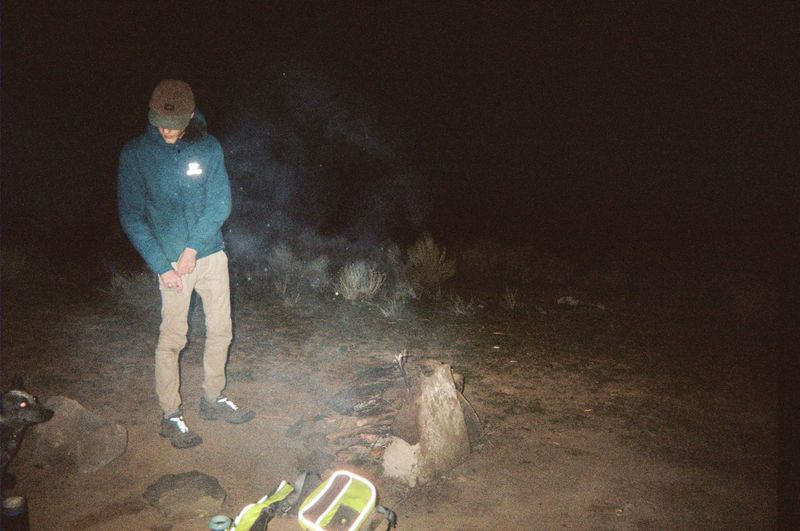 Midsection of man standing on land at night