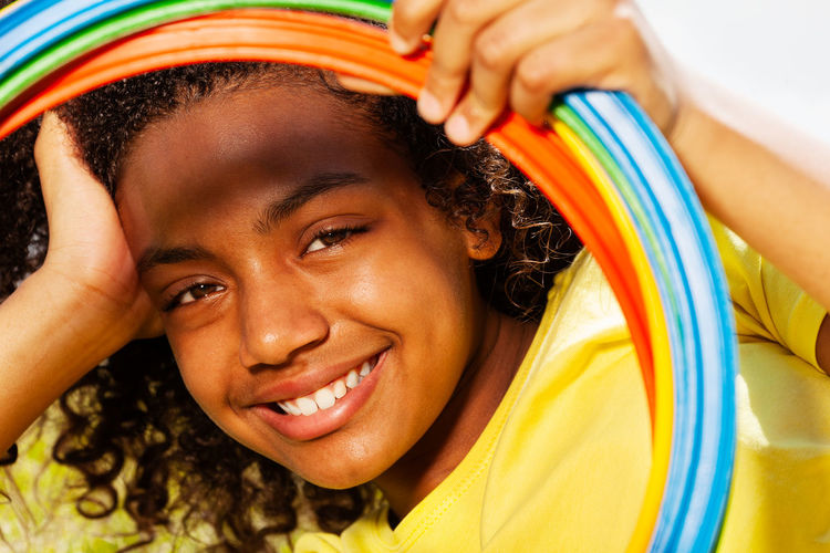 Close-up portrait of smiling girl looking through plastic hoops