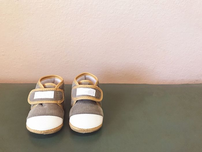 Babyboy Baby Babyhood Shoe Pair Still Life Indoors  Copy Space Two Objects No People Personal Accessory White Color Holiday Group Of Objects Absence Beach Slipper  Flip-flop Table Brown Wall - Building Feature Sport Sandal