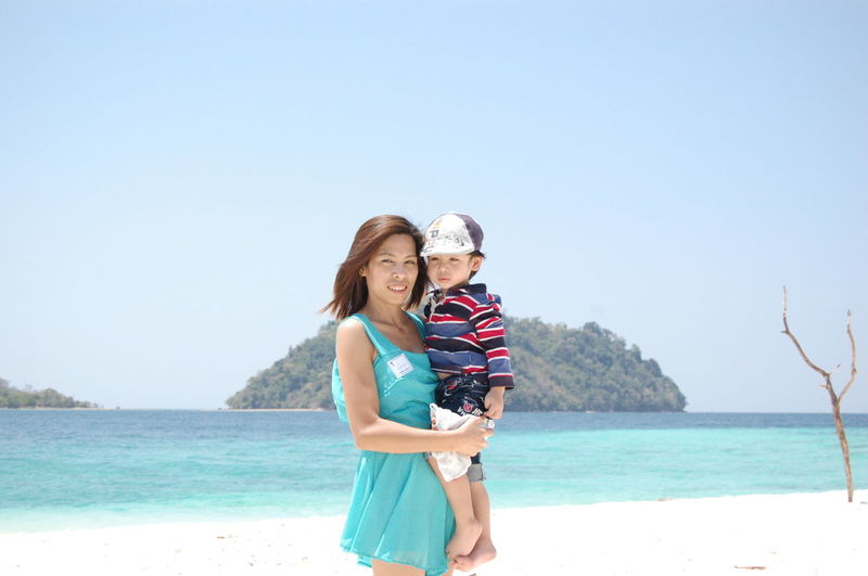 Portrait of mother carrying son while standing against sea