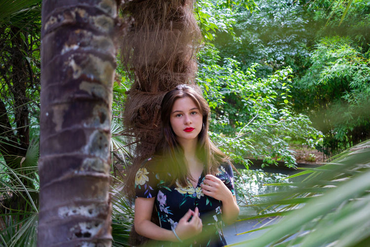 Portrait of young woman in tree trunks