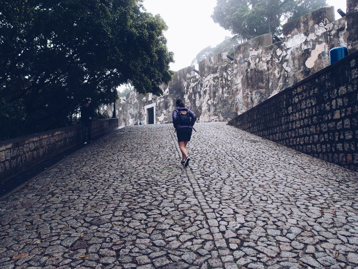 Rear View Of Woman Walking On Footpath At Fortaleza Do Monte