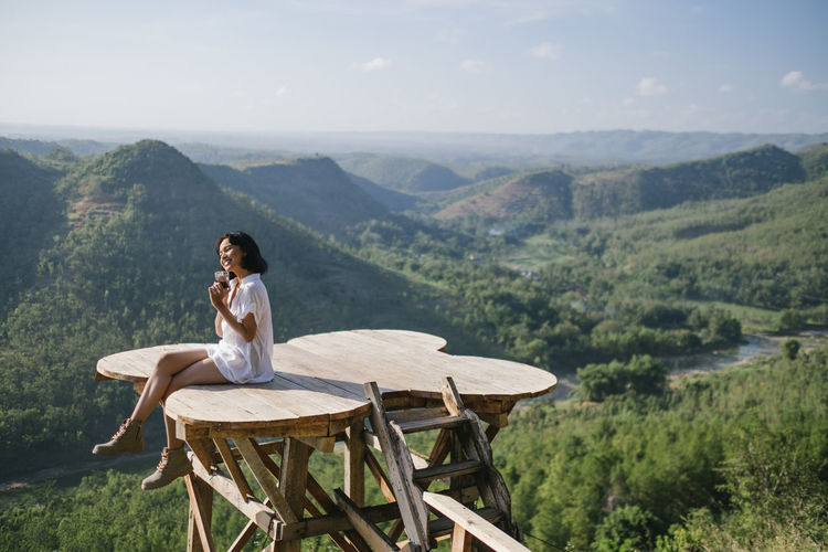 Full length of woman sitting at observation point against mountains and sky