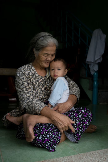 I met this amazing lady and her grandson whilst walking around a small farming village near Hoi An. She had an unbelievable calm and grace to her, and the boy she was holding wasn't at all bothered about this stranger in his front yard. Grandparents play a vital role in childcare in these villages, and I felt privileged to capture their bond on camera Grandmother Love Guardian Caring Travels Safe From Harm