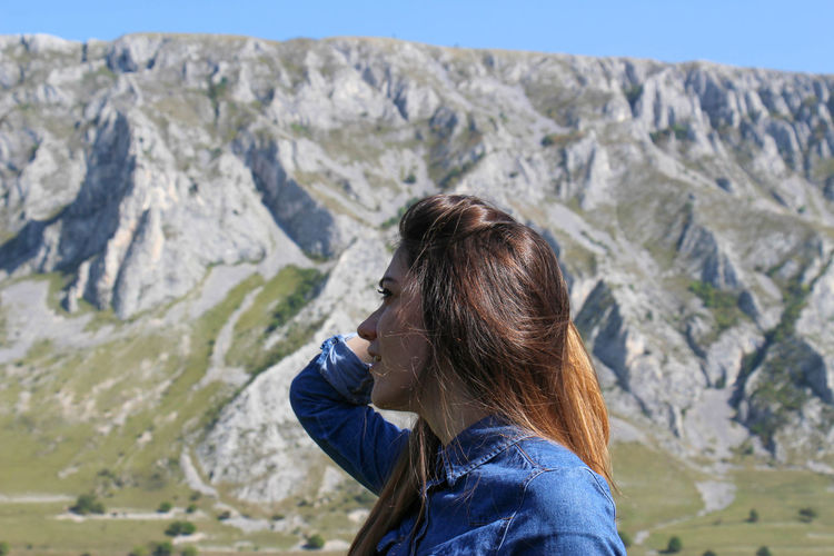 Side view of woman with hand in hair standing against mountains