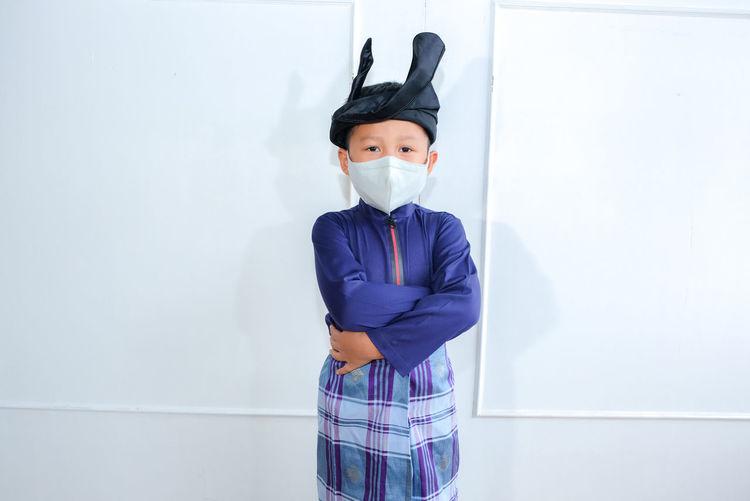 Kids portrait with baju melayu eid fitr celecration. boy using face mask cause of covid-19outbreak.