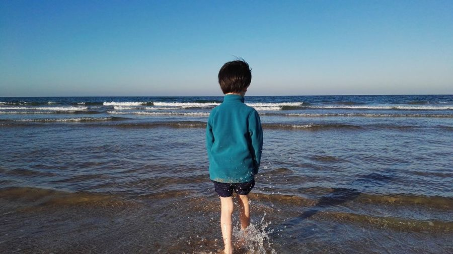 Rear view of boy walking at beach against clear blue sky