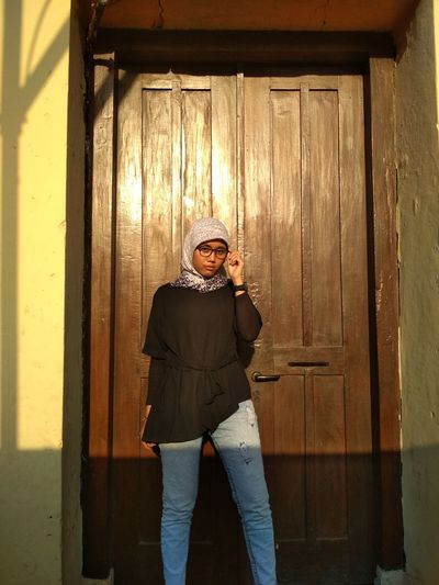 Woman wearing hijab standing by door