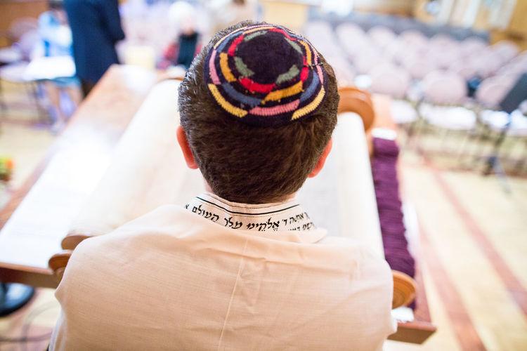 Rear view of jewish boy reading talmud