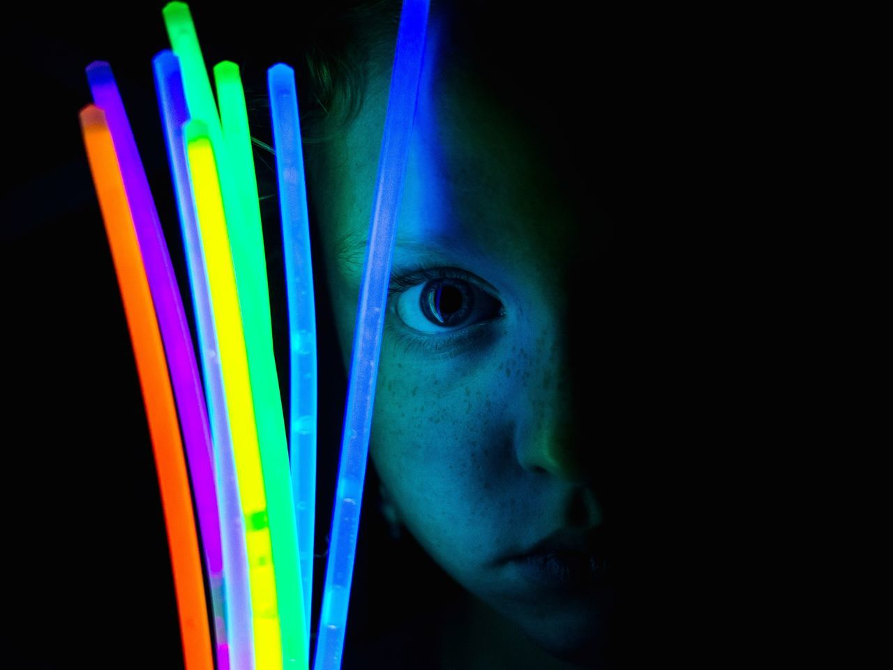 Portrait of girl holding glow sticks against black background