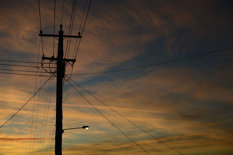 Low angle view of silhouette electric pole against sky during sunset
