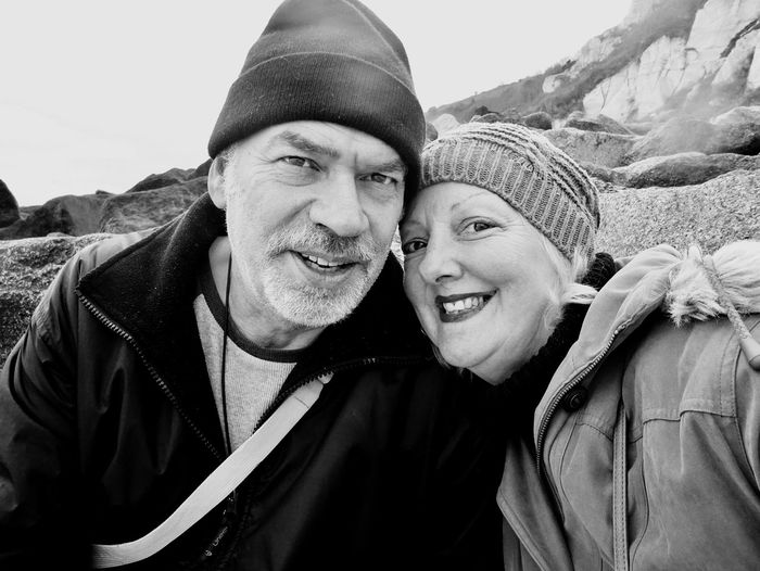 Close-up portrait of cheerful mature couple wearing warm clothing at beach