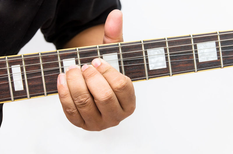 Close-Up Of Man Playing Guitar Against White Background