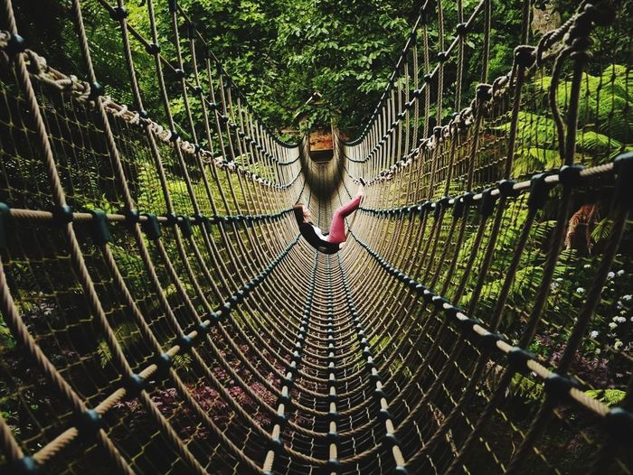 Side View Of Woman Sitting On Rope Bridge