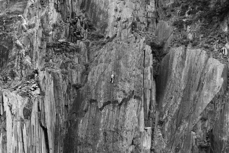 One person climbing dangerous mountain