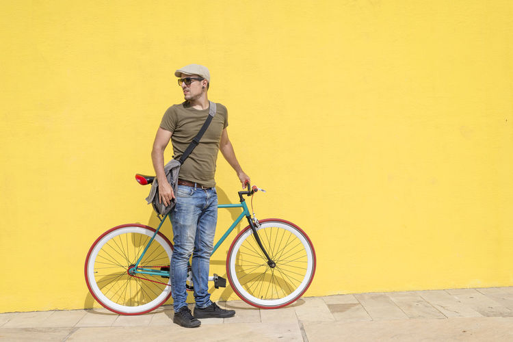 Mid adult man with bicycle standing against yellow wall