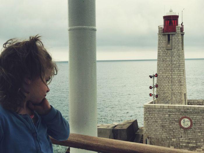 Girl standing at railing against sea