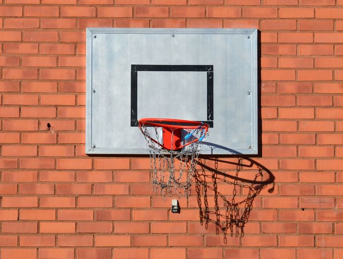Low angle view of basketball hoop against brick wall