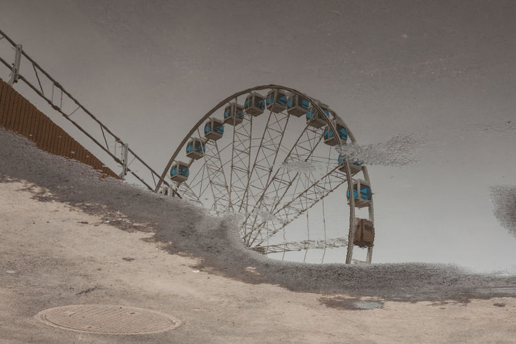 Asphalt Ferris Wheel Puddleography Leisure Activity Puddle Reflections Street Streetphotography Summer Tarmac Upside Down Water Rethink Things Going Remote
