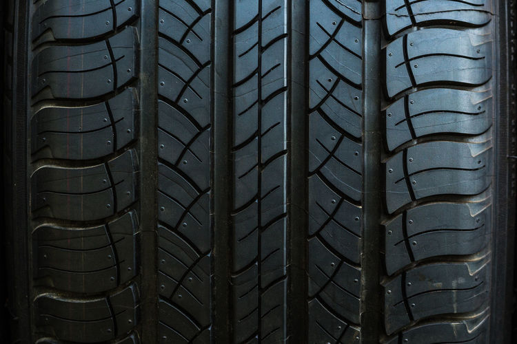 Close up on a tire on a dark background Architecture Backgrounds Car Close-up Day Isolated, No People Outdoors Pattern Shape Sky Tire Under, Vehicle