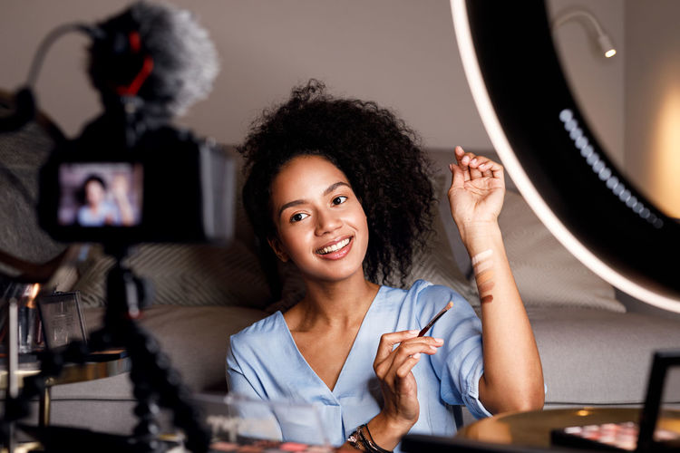 Indoors  Technology Portrait Woman Online Courses Makeup Artist Filming Video Vlogger Blogger Ring Light Sitting Looking Camera Home Brush Smiling Recording Lifestyle Livestreaming Selective Focus Modern Social Media
