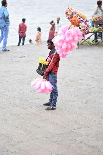 Rear view of women dancing on pink umbrella