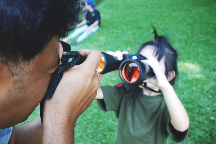 Father Photographing Girl Looking Through Binoculars While Standing On Field