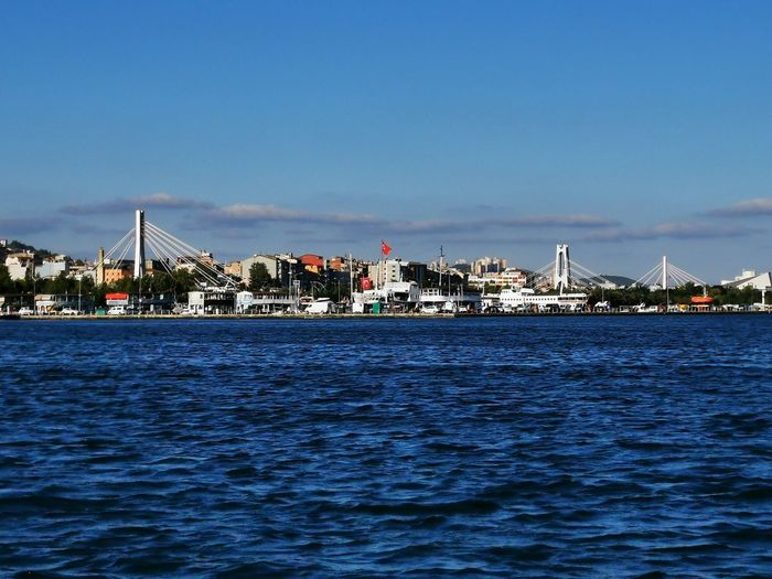 Sea by city buildings against blue sky