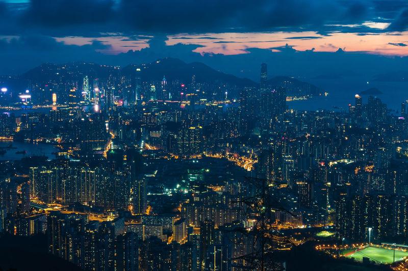 High angle view of illuminated city against sky at night in hong kong