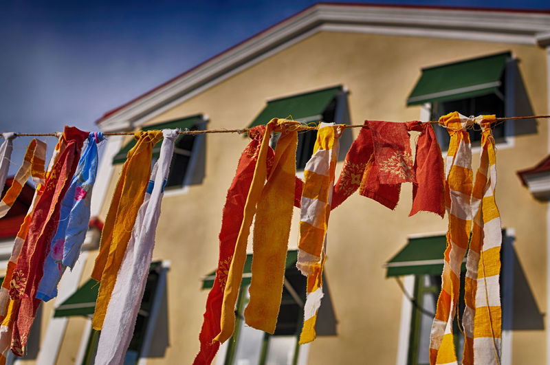 Colorful festiv rags on a cloth line. Blue Sky Building Clothing Line Colorful Festival Festive Gay Hanging HDR Rags