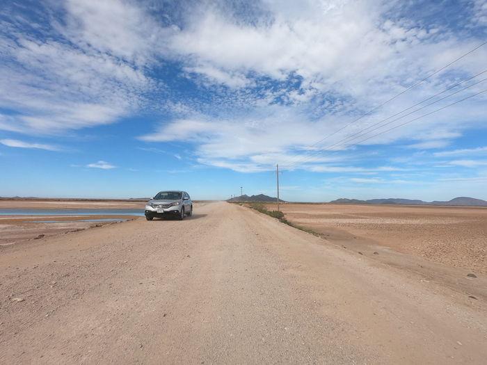 Car on road amidst desert against sky