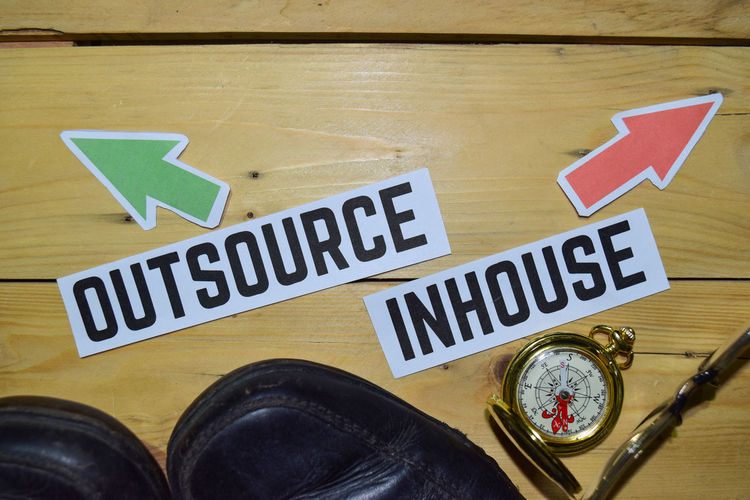 Outsource or Inhouse opposite direction signs with boots,eyeglasses and compass on wooden vintage background. Business, education and finance concepts Inhouse Business Outsourcing Outsource Company Contract Job Freelance Employment Recruitment Development Marketing Hiring Budget Sign Employee Consulting Hire Vacancy Concept Choice Planning Management Subcontract In-house