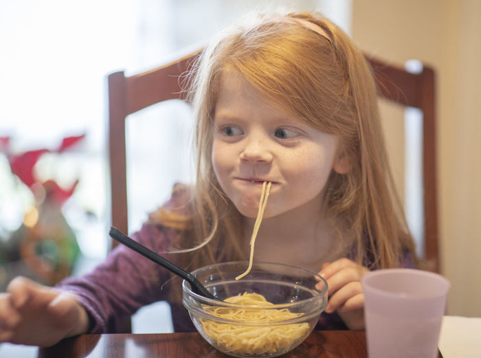 A five-year-old girl slurps up a spaghetti noodle during dinner. Child Food And Drink Childhood Portrait Food Girls Headshot Bowl Focus On Foreground One Person Kitchen Utensil Front View Table Spoon Indoors  Females Eating Utensil Holding Innocence Glass Hairstyle Breakfast Spaghetti Noodles Slurp