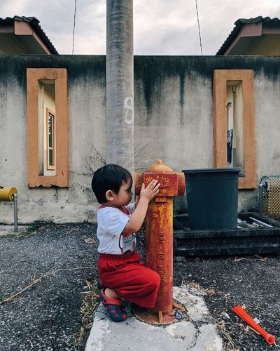 Full Length Of Boy Holding Fire Hydrant Against Building