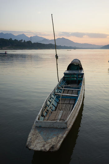 ASIA Beauty In Nature Calm Day Mekong River Moored Mountain Nature Nautical Vessel No People Outdoors Reflection Riverview Scenics Sea Sky Small Boat Sunset Sunset_collection Traditional Boat Tranquility Travel Destinations Travel Photography Water Waterfront