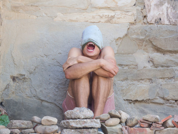 Shirtless Young Man Screaming While Sitting By Wall