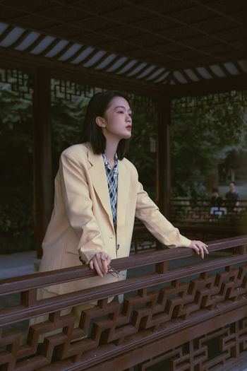 Portrait of young woman looking away while standing on railing