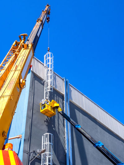 Low angle view of crane and building against clear blue sky