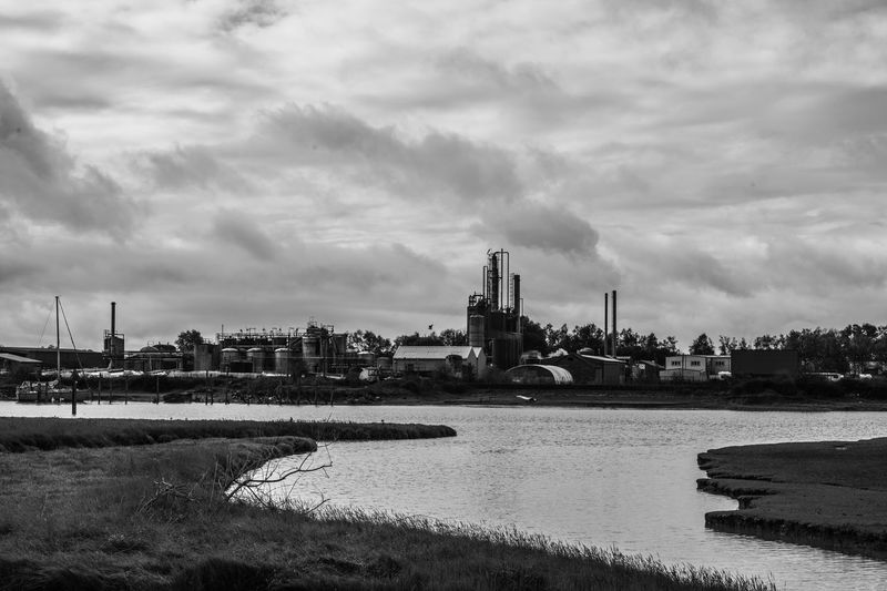 River by factory against sky in city