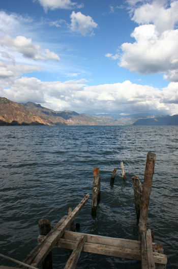 """The end of the """"road"""". Atitlan Lake, Guatemala. Atitlan Lake Beauty In Nature Cloud - Sky Day Lake Mountain Nature No People Outdoors Scenics Sky Tranquil Scene Tranquility Water Wood - Material"""